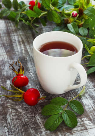 teaparty: Tea from a dogrose in a mug on a wooden background with fruits