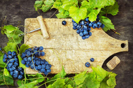 Grapes and old board on a wooden background