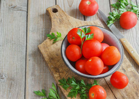 red tomatoes on a wooden boardwith parsley . country style. Stock Photo