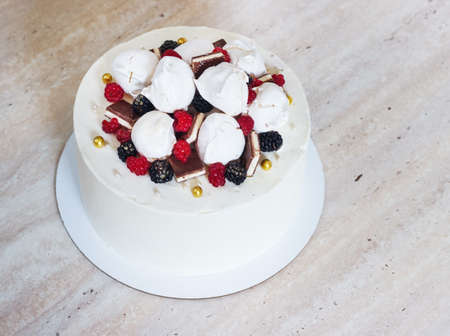 White festive cake with meringue and berries