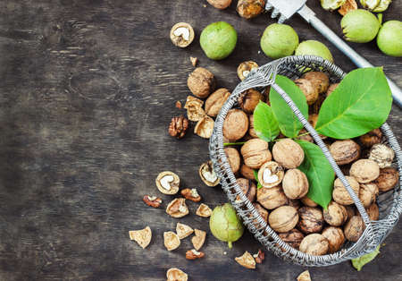 Whole Walnuts and Cleared in the basket Black Wooden Background Top view Healthy concept.