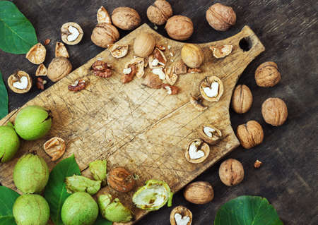 Whole Walnuts and Cleared Black Wooden Background Top view Healthy concept