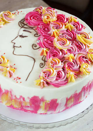 Festive cake with cream flowers and a girl face on a light background