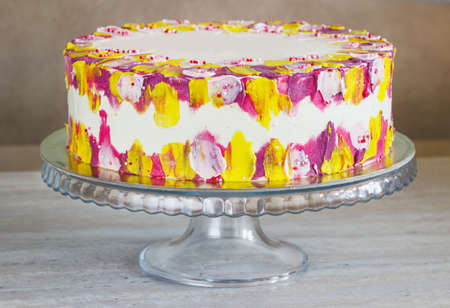 White Birthday cake with colorful Sprinkles over a light background