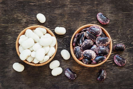 white and dark beans on a dark wooden background in a cup