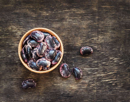 dark beans on a dark wooden background in a cup Stock Photo