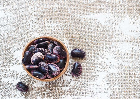 Dark beans on a light background in a wooden cup. Stock Photo