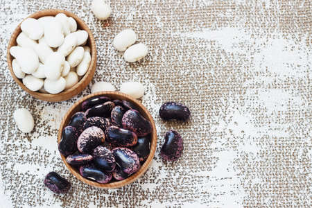 Different types of legumes - Cannellini Beans, Black and Red Kidney Beans, Lima and Pinto Beans had sorted in wooden bowls. Stock Photo