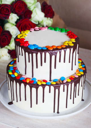 White Birthday cake with colorful Sprinkles over a light background with a bouquet of roses