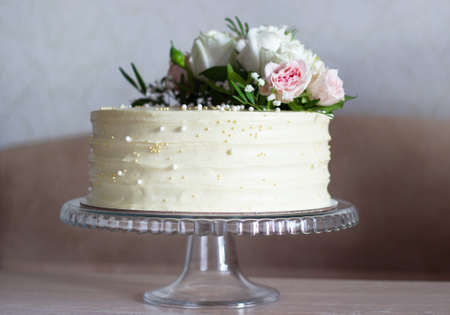Beautiful Wedding cake with flowers on marble table and white background