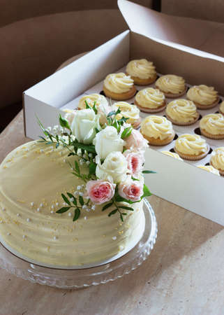 wedding cake with fresh flowers and cupcakes on a light background 免版税图像