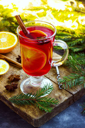 Mulled wine with spices and Christmas tree on dark background. Banque d'images - 128616147