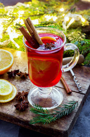 Mulled wine with spices and Christmas tree on dark background