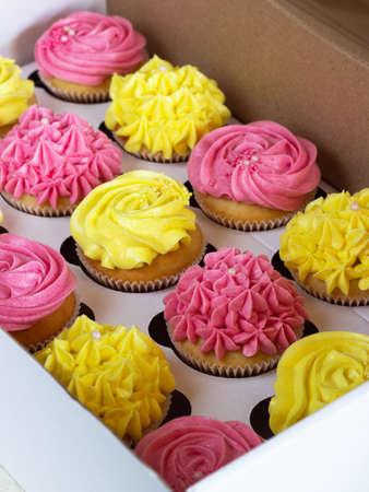 Delicious cupcakes in cardboard box .