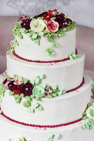 Festive four-level white elegant cake with cream flowers, wedding cake, cream flowers in the Malaysian technique.