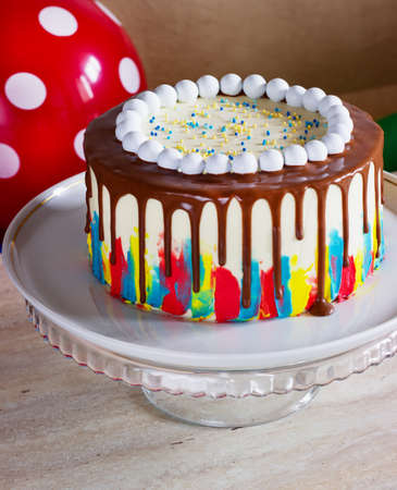 bright birthday cake with chocolate on a light background with balloons Reklamní fotografie