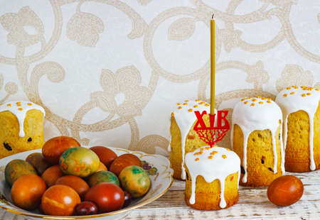 Easter composition with orthodox sweet bread, kulich and eggs on light background. Easter holidays breakfast concept Reklamní fotografie