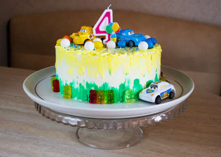 Childrens colorful fondant birthday cake decorated with little cars