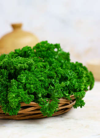 Fresh green parsley in a wicker wooden basket on a light background