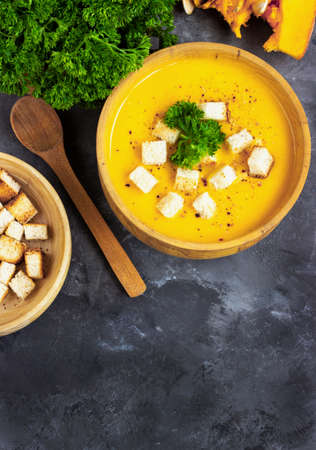 Pumpkin soup with cream, bread and fresh parsley in a rustic metal plate over grunge black background. Top view, copy space