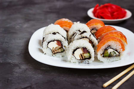 sushi rolls on a white plate on a black background with pickled ginger