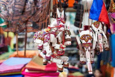 títere: Venta de recuerdos en el mercado, Siem Reap, Camboya. Divertidos muñecos de madera hechos a mano burros y elefantes con arnés de colores brillantes. Editorial