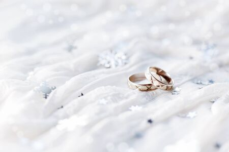 winter wedding: Wedding rings on white holiday background with sparkling silver snowflakes, christmas decorations. Symbol of wedding in winter time.