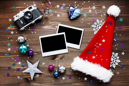 Christmas and New Year background with old fashioned camera, red Santa's hat, photo frames and christmas decorations - balls, stars, silver sparkling snowflakes, confetti on wooden table. Place for your text.