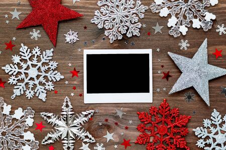 Christmas and New Year background with decorations - balls, stars, silver sparkling snowflakes and confetti on wooden table. Empty photo frame. Mock up.
