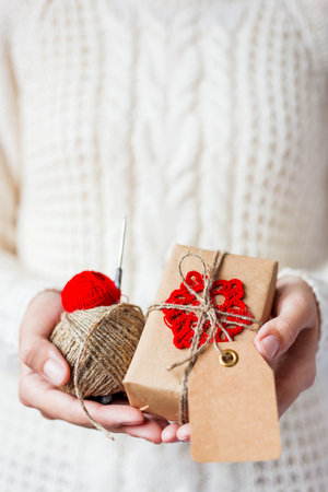 the snowflake: Woman in white knitted sweater and mitts holding a present and coils of red thread and linen rope. Gift is packed in craft paper with hand made crocheted red snowflake. Present has an empty tag for your text. Mock up. Example of DIY ways to pack Cristmas  Stock Photo