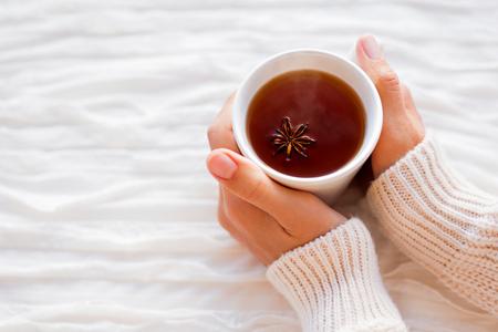 calor: Las mujeres sostienen una taza de té caliente con anís estrellado. Mañana acogedora en el país.
