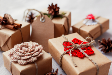 Christmas presents with hand made decorations - crocheted flower and snowflake, pine cones, vanilla pods. DIY decorations for wrapped in craft paper gifts. Stockfoto