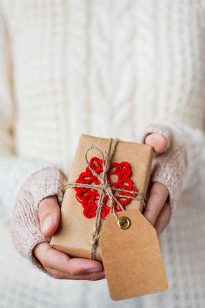 Woman in white knitted sweater and mitts holding a present. Gift is packed in craft paper with hand made crocheted red snowflake. Present has an empty tag for your text. Mock up. Example of DIY ways to pack Cristmas and other presents.