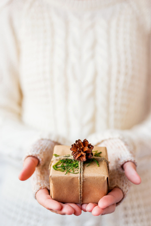 Woman in knitted sweater holding a present. Gift is packed in craft paper with pine cones and tied with rough rope. Example of DIY way to wrap a present. Place for your text.