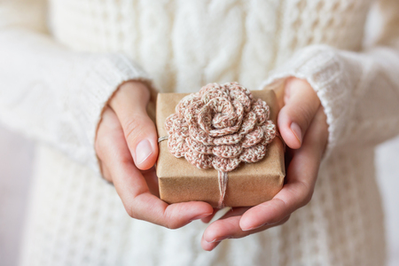 xmas crafts: Woman in white knitted sweater holding a present. Gift is packed in craft paper with hand made crocheted flower. Example of DIY ways to pack Cristmas and other presents. Stock Photo