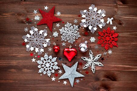 retro backgrounds: Christmas and New Year background with christmas decorations - balls, stars, silver sparkling snowflakes and confetti on wooden table. Heart shape.