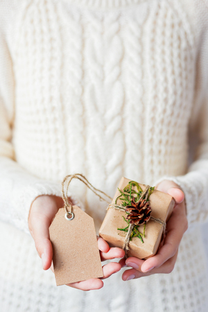 Woman in knitted sweater holding a present. Gift is packed in craft paper with pine cones and tied with rough rope. Empty tag for your text. Mock up. Example of DIY way to wrap a present.