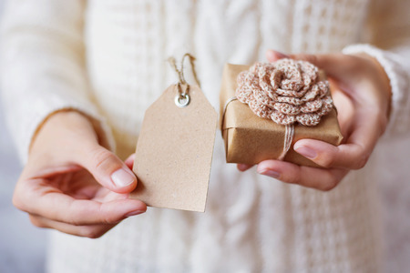 Woman in white knitted sweater holding a present. Gift is packed in craft paper with hand made crocheted flower.Empty tag for your text. Mock up. Example of DIY ways to pack Cristmas and other presents.