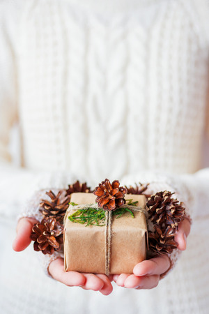 Woman in knitted sweater holding a present. Gift is packed in craft paper with pine cones and tied with rough rope. Hands full of pine cones. Example of DIY way to wrap a present.