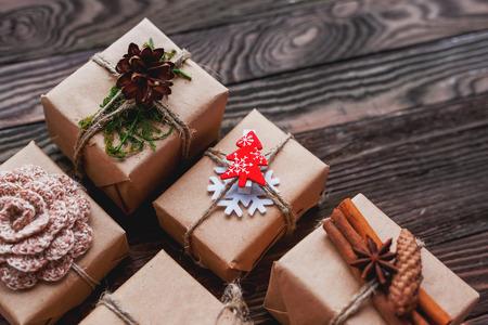 wraps: Regalos de Navidad con decoraciones hechas a mano - ganchillo flor y copo de nieve, piñas, vainas de vainilla. decoraciones de bricolaje para regalos envueltos en papel del arte. El lugar de texto.