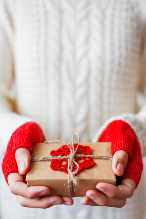 mitts: Woman in white knitted sweater and mitts holding a present. Gift is packed in craft paper with crocheted red snowflake. Example of DIY way to wrap a gift. Stock Photo