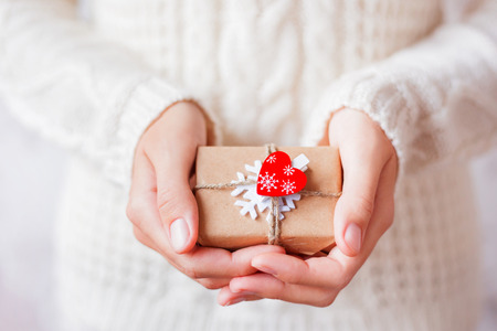 Woman in knitted sweater holding a present. Gift is packed in craft paper with white felt snowflake and red heart. DIY way to pack Christmas presents. Banque d'images