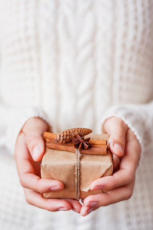 Woman in knitted sweater holding a present. Gift is packed in craft paper with vanilla pods, fir cone and star of anise. DIY way to pack Christmas presents. Place for text.