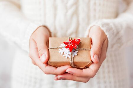 Woman in knitted sweater holding a present. Gift is packed in craft paper with white felt snowflake and red fir tree. DIY way to pack Christmas presents. Banque d'images