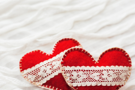 ruche: White fabric background with ruche.Two felt hearts with laces, symbol of love. Good for Valentines Day cards. Place for text.