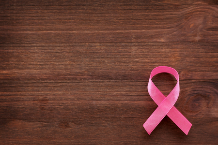 Pink ribbon - symbol of breast cancer awareness. Wooden background. Good as background for World Cancer Day posters, printed materials.