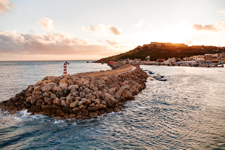 seafront: Entrance in bay, seafront with lighthouse on seafront at sunset. Gozo, Malta. Stock Photo
