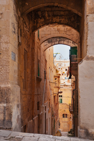 mediterranian houses: Ancient Eagle street in Valletta, Malta. Naroow street with old fashioned balcony, carved stone walls and arches. Editorial