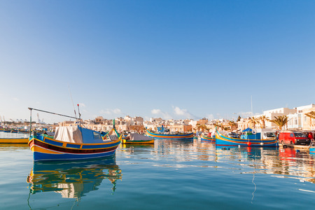 fisherman: Colorful typical boats - Mediterranean traditional fisherman village in the south east of Malta. Early winter morning in Marsaxlokk, Malta.