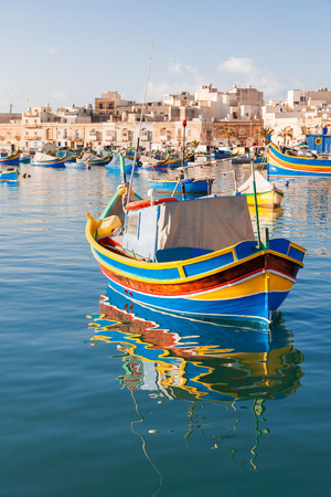 Colorful typical boats - Mediterranean traditional fisherman village in the south east of Malta. Early winter morning in Marsaxlokk, Malta.